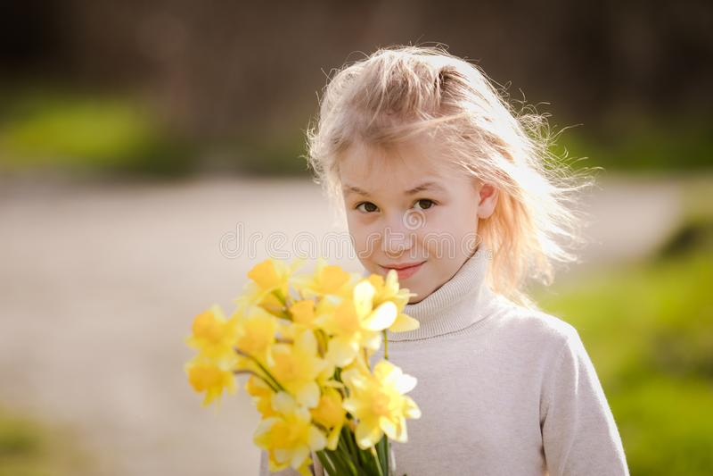 Petite fille heureuse blonde mignonne avec le pays jaune de jonquilles au printemps images libres de droits