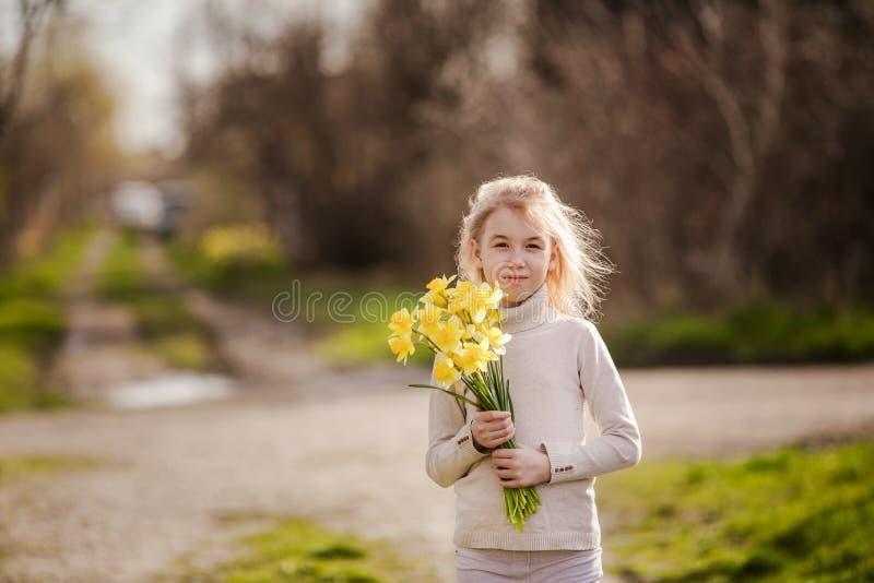 Petite fille heureuse blonde mignonne avec le pays jaune de jonquilles au printemps photo stock