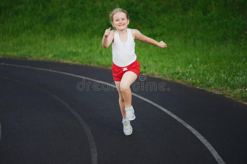 Petite fille heureuse courant sur le stade images stock
