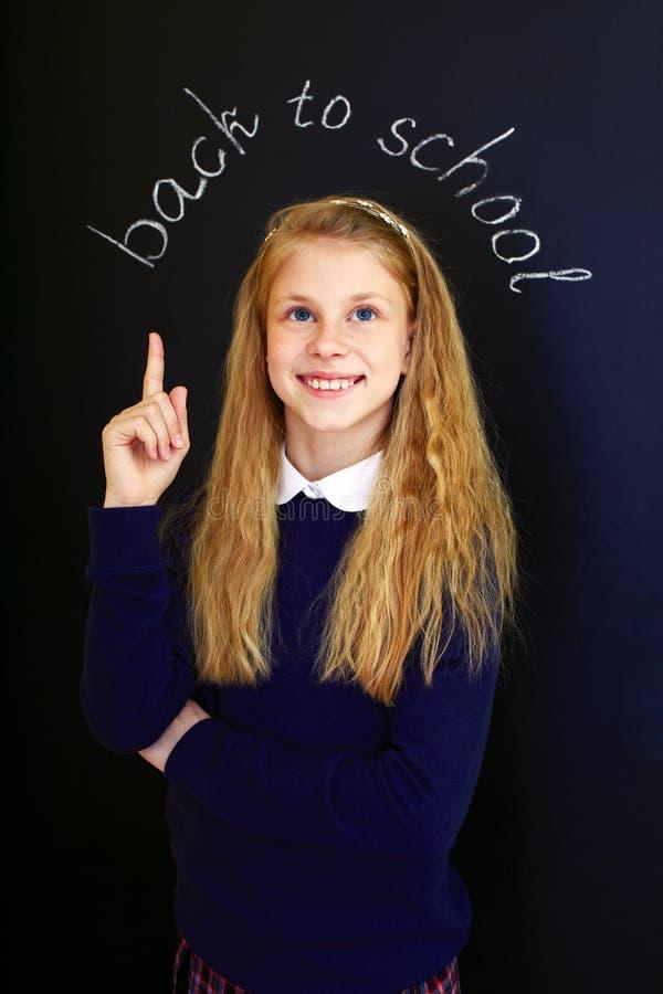 Petite fille heureuse d'école près de tableau noir d'école images libres de droits