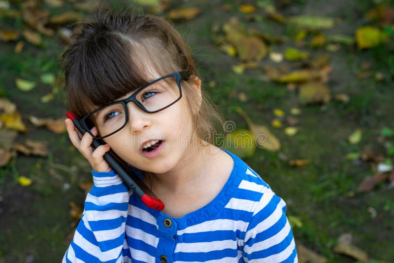 Petite fille heureuse d'enfant avec des yeux bleus regardant in camera avec l'expression heureuse et paisible en verres, se tenan image stock