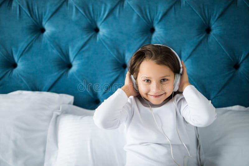 Petite fille heureuse dans des pyjamas écoutant la musique tout en se reposant dans son lit photo libre de droits