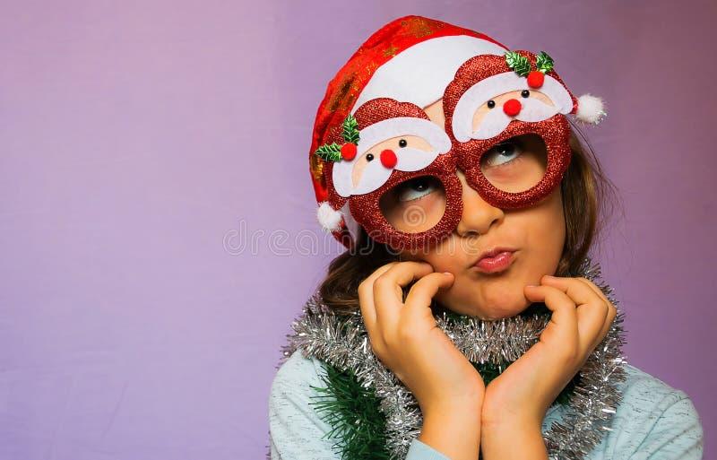 Petite fille heureuse en chapeau et verres de Santa s photographie stock libre de droits