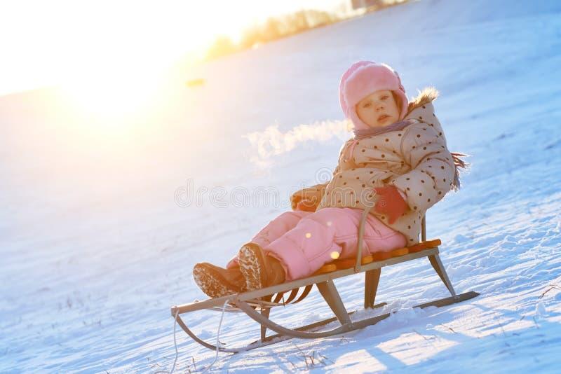 Petite fille heureuse en hiver sur le traîneau photos stock