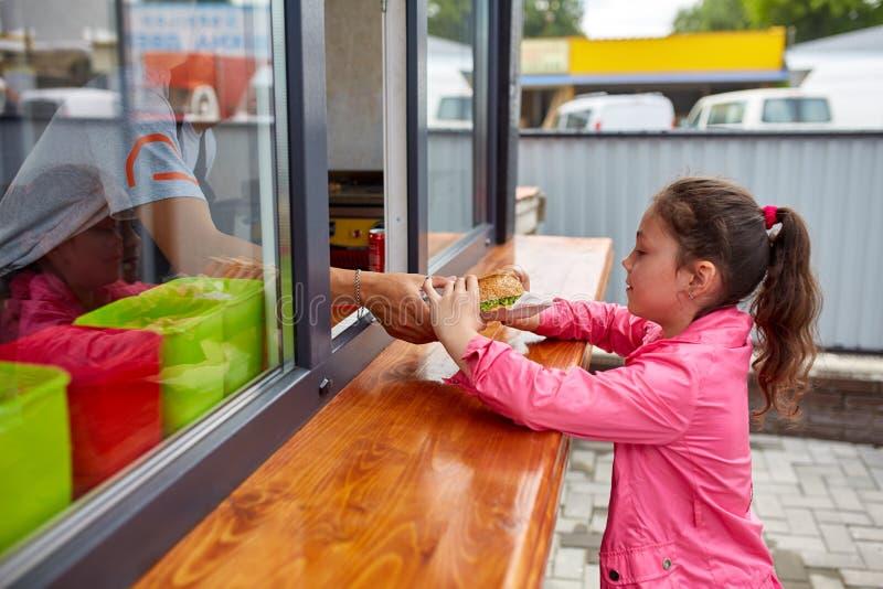 Petite fille heureuse enlevant son hamburger par la fenêtre de boutique de rue photo stock