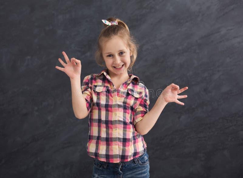 Petite fille heureuse grimaçant au fond gris photos stock