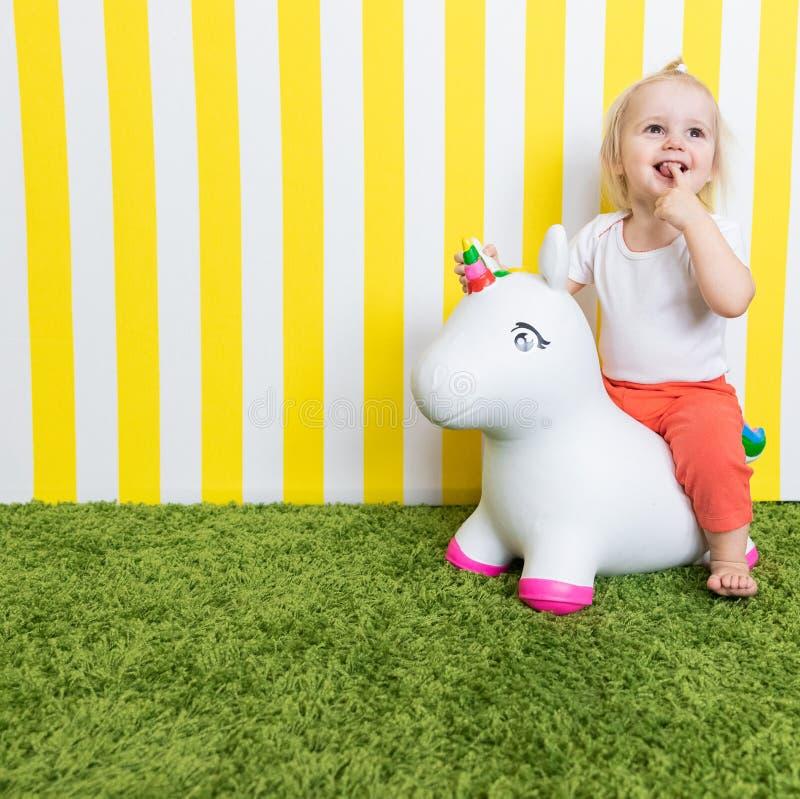 Petite fille heureuse intelligente sur Toy Unicorn Enfance Fond images stock