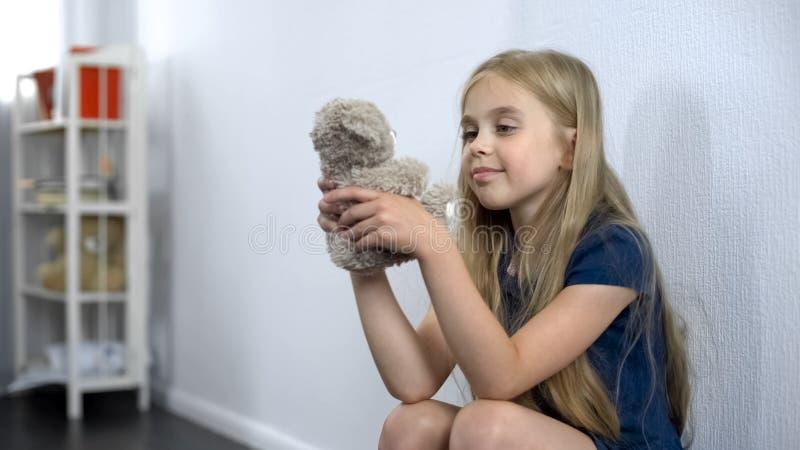 Petite fille heureuse jouant avec l'ours de nounours au jardin d'enfants, ayant l'amusement, enfance photos libres de droits