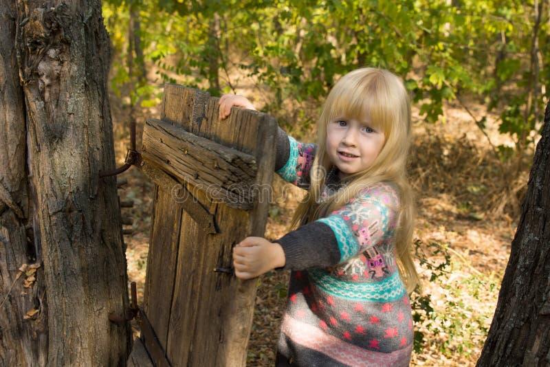 Petite fille heureuse jouant avec une porte rustique photos stock