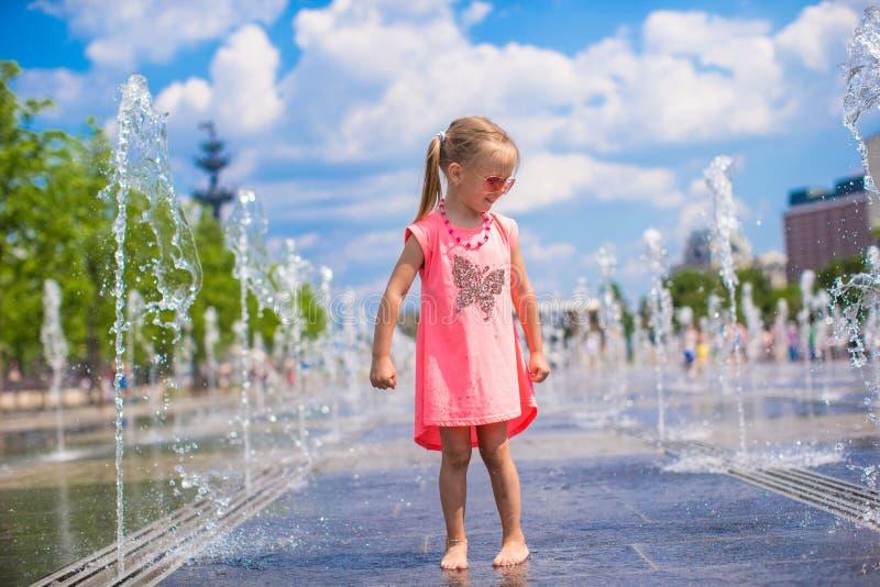 Petite fille heureuse jouant dans la fontaine ouverte de rue image libre de droits