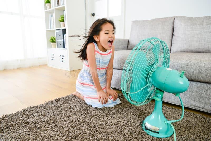 Petite fille heureuse jouant le ventilateur électrique à la maison images libres de droits