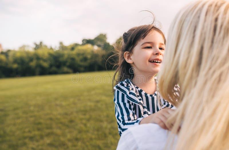 Petite fille heureuse mignonne riant et jouant avec sa jolie maman en parc La mère et la fille aimantes passent le temps ensemble photographie stock libre de droits