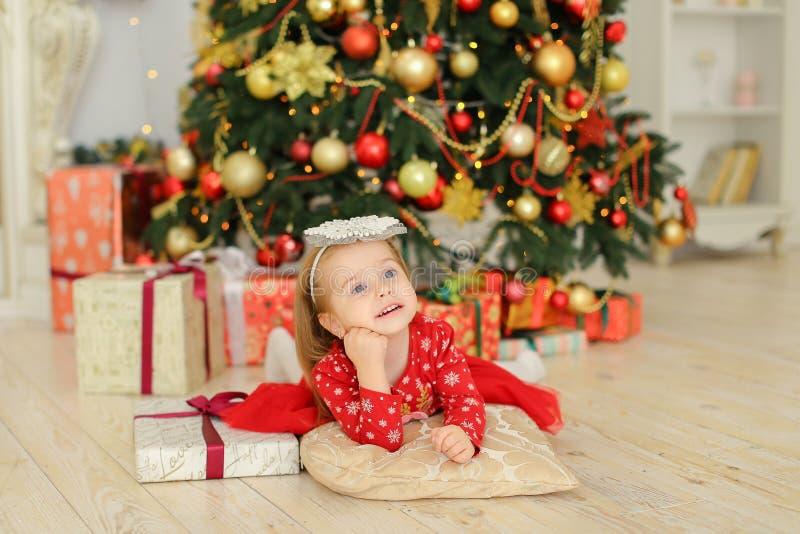 Petite fille heureuse portant la robe rouge se trouvant près de l'arbre et des présents de Noël photo libre de droits