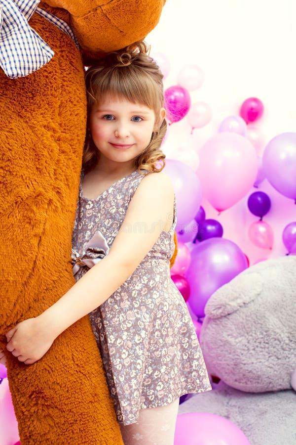 Petite fille heureuse posant étreignant le grand ours de nounours image stock