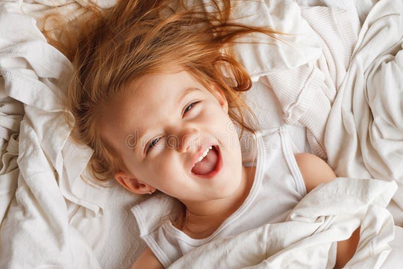 Petite fille heureuse s'étendant dans la blanchisserie photos stock