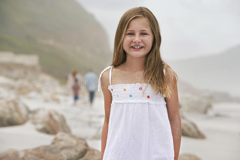 Petite fille heureuse se tenant sur la plage photo stock