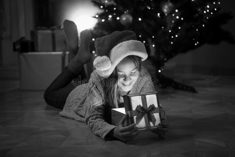 Petite fille heureuse se trouvant avec le boîte-cadeau sous l'arbre de Noël image libre de droits