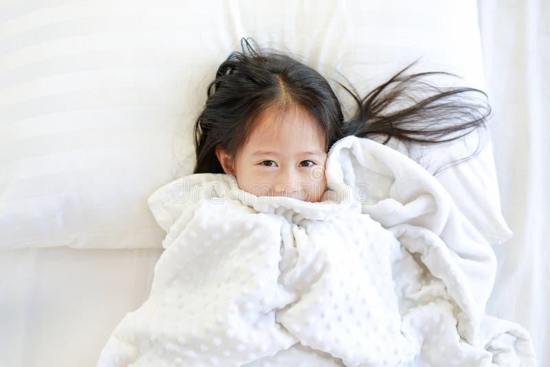 Petite fille heureuse se trouvant sur le lit avec la couverture et regardant la caméra Vue supérieure images stock