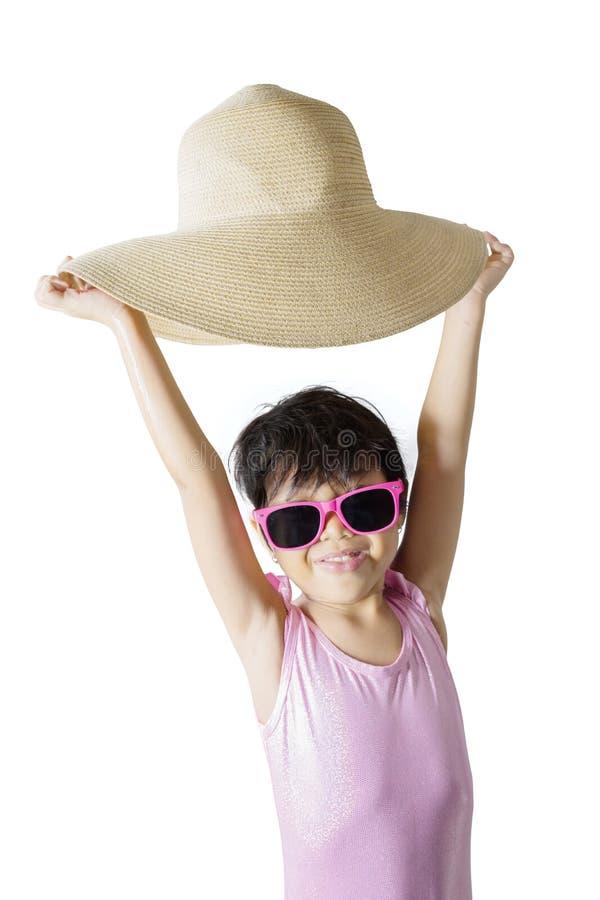Petite fille heureuse soulevant son chapeau sur le studio photographie stock libre de droits