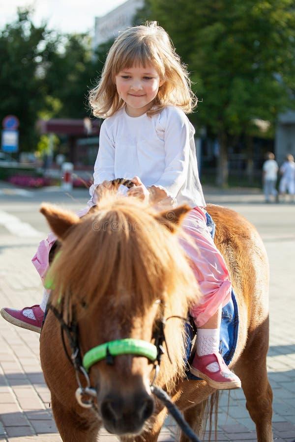 Petite fille heureuse sur un poney images stock