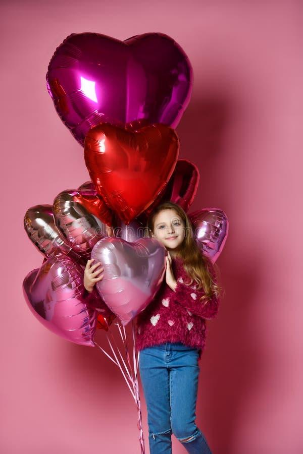 Petite fille heureuse tenant un ballon en forme de coeur photos libres de droits