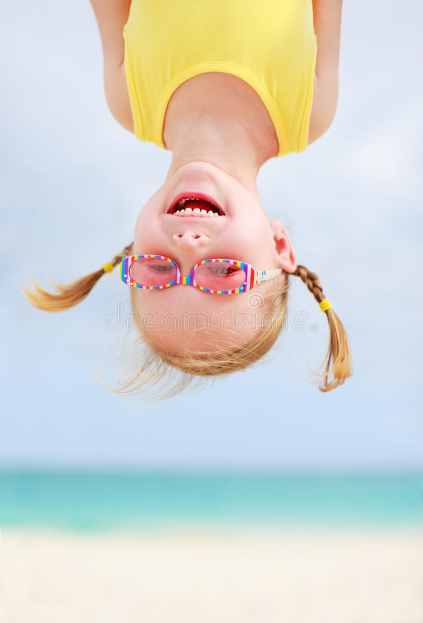 Petite fille heureuse upside-down photographie stock