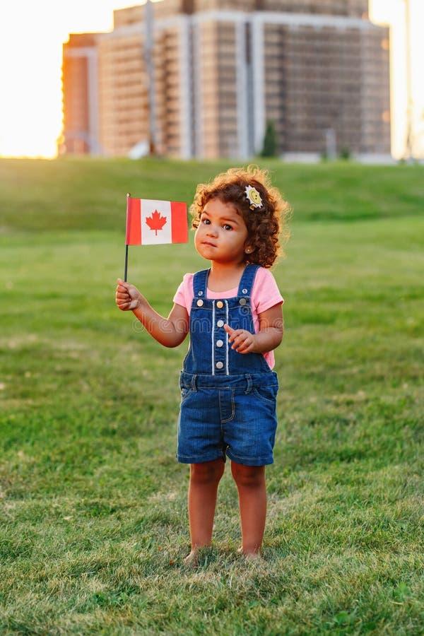 Petite fille hispanique latine d'enfant en bas âge de bébé tenant le drapeau canadien de ondulation photo stock