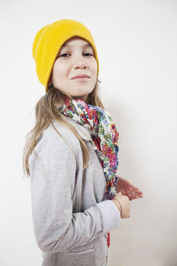 Petite fille idiote dix années dans le chapeau de tricotage jaune photo stock