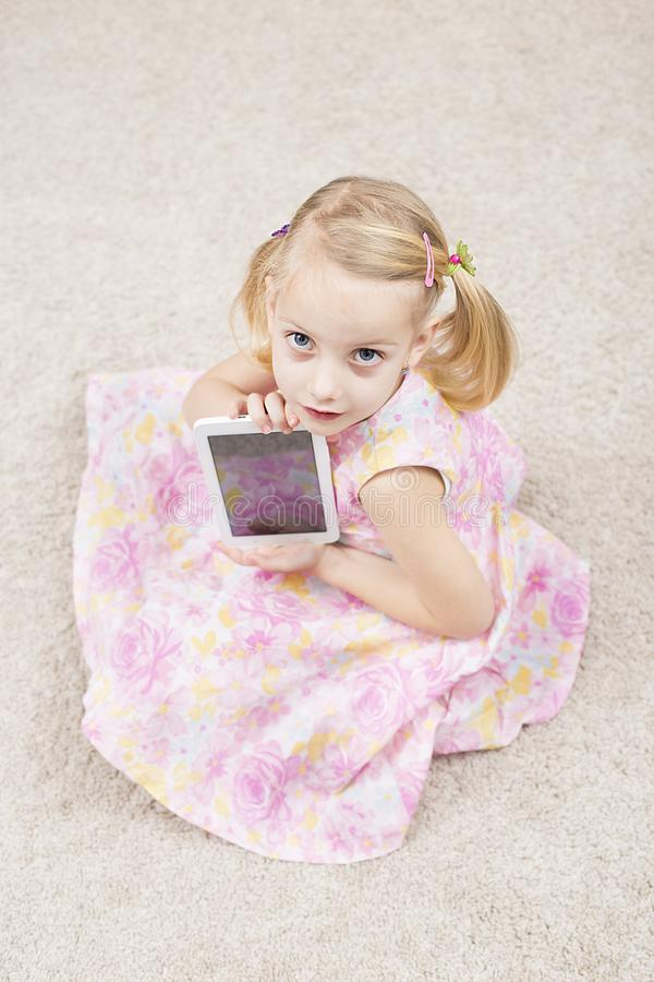 Petite fille intelligente avec le tablete photos libres de droits
