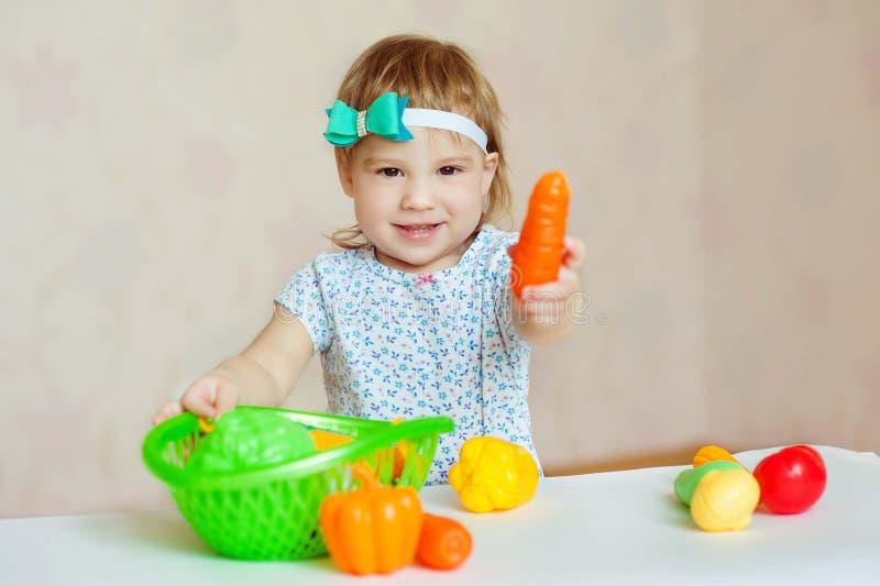 Petite fille jouant à l'intérieur à la maison ou jardin d'enfants Légumes de sourire adorables de plastique de coupe de petit enf image libre de droits