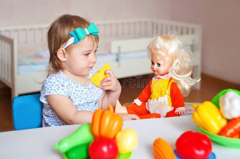 Petite fille jouant à l'intérieur à la maison ou jardin d'enfants Légumes en plastique de sourire adorables de coupe de petit enf image libre de droits