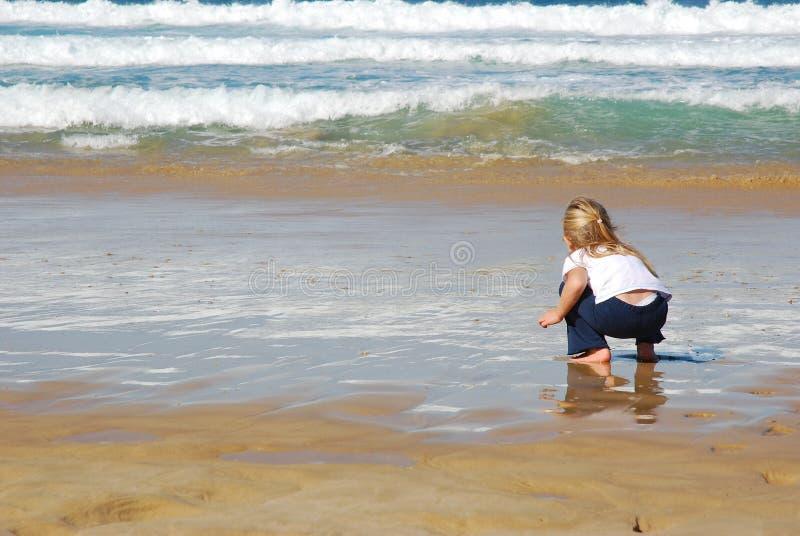 Petite fille jouant à la plage image libre de droits