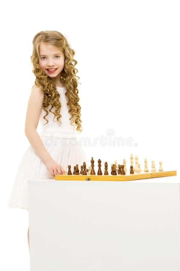 Petite fille jouant aux ?checs Une petite fille joue des ?checs Le concept de l'éducation créative d'un enfant, formation de photo stock