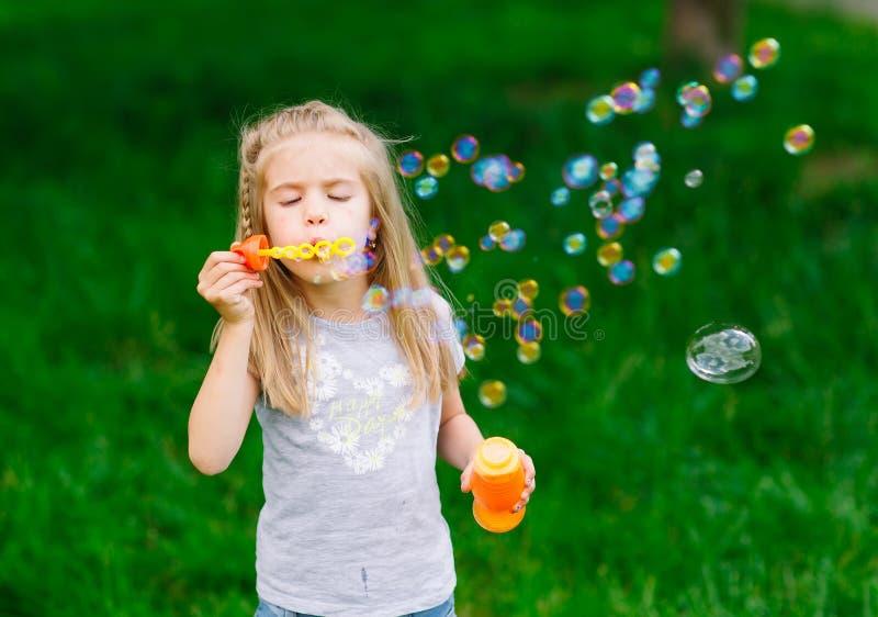 Petite fille jouant avec des bulles de savon en parc image libre de droits