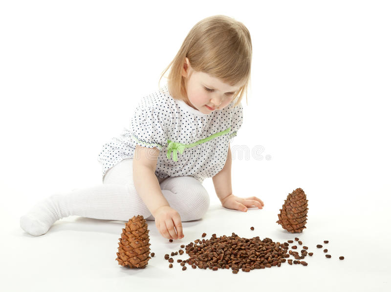 Petite fille jouant avec des cônes de cèdre photo libre de droits