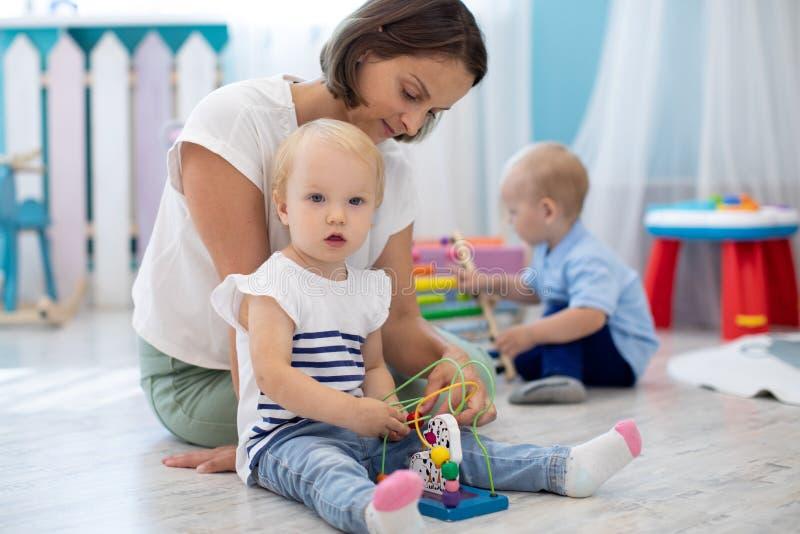 Petite fille jouant avec des jouets avec un professeur ou une baby-sitter à l'intérieur photos libres de droits