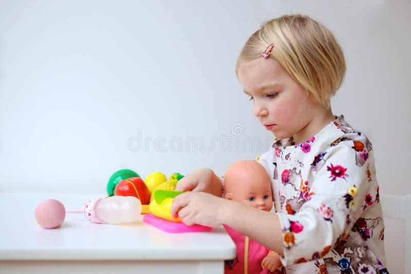 Petite fille jouant avec la poupée photographie stock