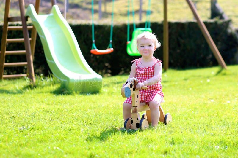 Petite fille jouant avec le cheval de roue dans le jardin photographie stock libre de droits