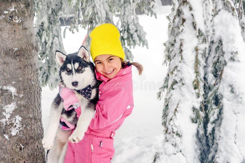 Petite fille jouant avec le chien enroué sur la neige photographie stock libre de droits