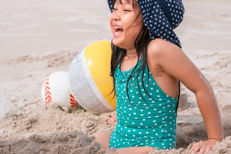 Petite fille jouant avec le sable à la plage tropicale en somme photographie stock libre de droits