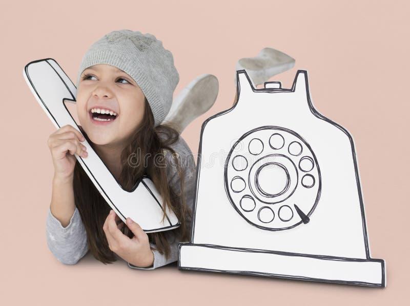 Petite fille jouant avec le téléphone de maquette photographie stock libre de droits