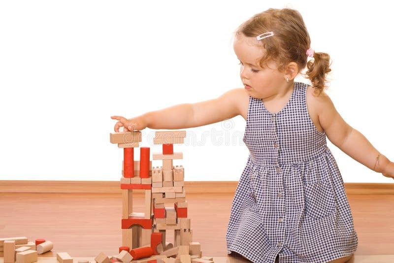 Petite fille jouant avec les blocs en bois images stock
