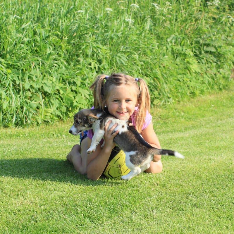 Petite fille jouant avec un chiot photo libre de droits