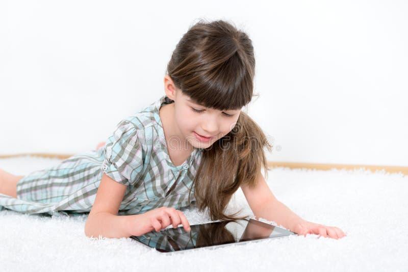 Petite fille jouant avec le comprimé d'ipad de pomme photographie stock libre de droits