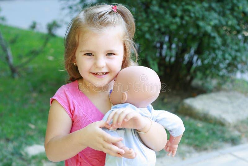 Petite fille jouant avec une chéri - poupée photos stock