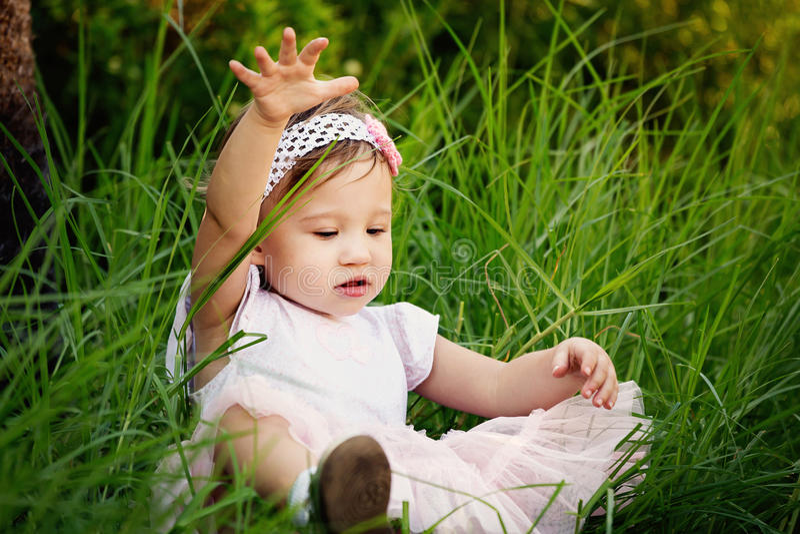 Petite fille jouant dans l'herbe photographie stock