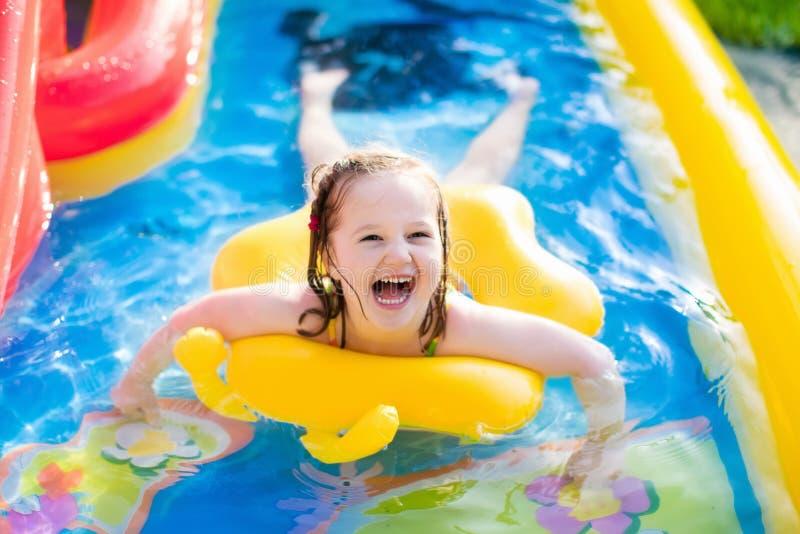 Petite fille jouant dans la piscine gonflable de jardin photographie stock