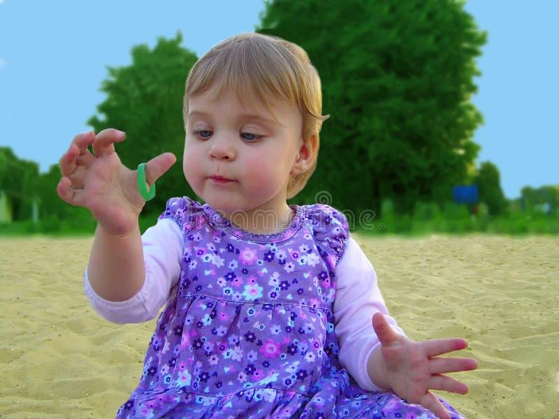 Petite fille jouant dans le sable sur la nature photos libres de droits