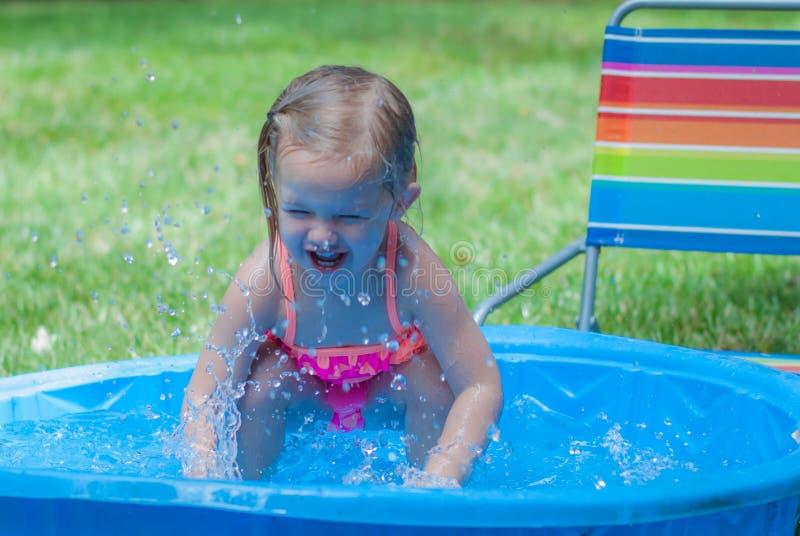 Petite fille jouant dans une piscine de Kiddie image libre de droits