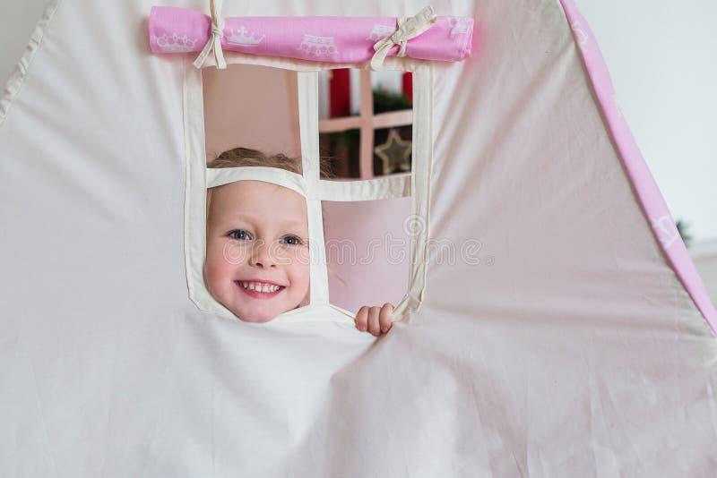 Petite fille jouant dans une tente photos stock